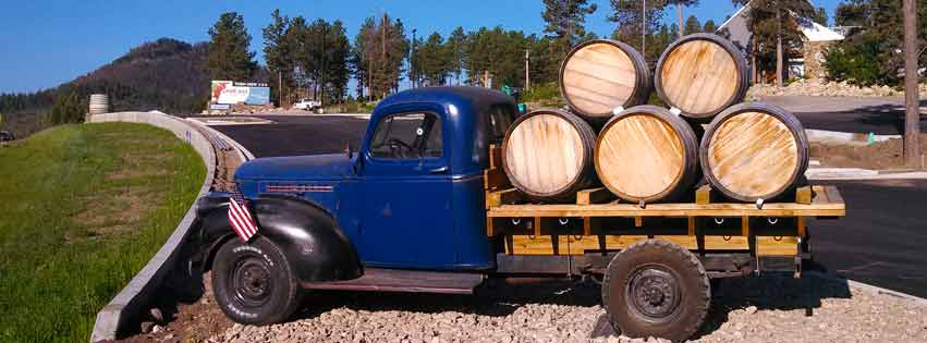 old blue truck with five barrels on the back